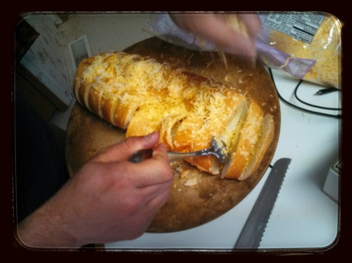 Adding Cheese to Cheesy Garlic Bread